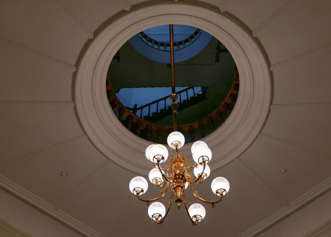 """Люстра. Через """"окно"""" в потолке видны фрагменты лестницы и перила... - Юрий Поляков"""