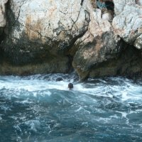 Парень из команды яхты ныряет с бортика яхты в море и плывёт к скале. :: Галина