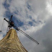 Церковный купол на фоне тёмных облаков и крана, который его поднимет :: Владимир Ростовский
