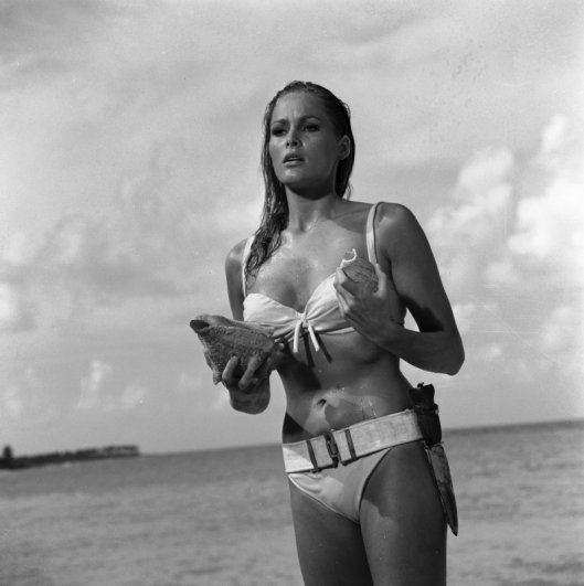 Emerging from the sea singing calypso 'Under the Mango Tree' Honey (Ursula Andress) is surprised to hear someone taking up the song refrain. Copyright Notice - © 1962 Danjaq, LLC and United Artists Corporation. All rights reserved.